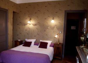 Lit double dans la chambre d'hôtel restaurant La Marbrerie, décor belle époque